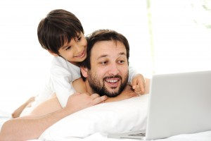 Father and son in bed, using laptop together, happy time